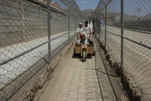 Men coming from Afghanistan move down a corridor between security fences at the border post in Torkham, Pakistan June 18, 2016. Reuters/Fayaz Aziz.