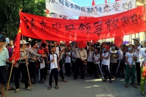"""Villagers carry banners which read """"Plead the central government to help Wukan"""" (in red) and """"Wukan villagers don't believe Lin Zuluan took bribes"""" during a protest in Wukan, China's Guangdong province June 22, 2016. REUTERS/James Pomfret"""