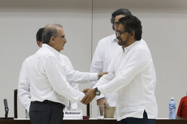 Colombia's lead government negotiator Humberto de la Calle and Colombia's FARC lead negotiator Ivan Marquez (right) shake hands in Havana, December 15, 2015. Credit: Reuters