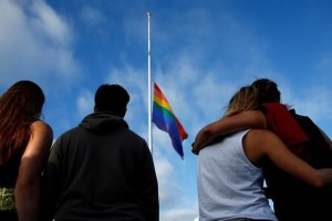 Mourners gather under a LGBT pride flag flying at half-mast for a candlelight vigil in remembrance for mass shooting victims in Orlando, from San Diego, California, US June 12. Credit: Reuters/Mike Blake/File Photo