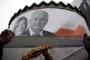 People walk past a giant picture of late Polish president Lech Kaczynski and his wife Maria, who died six years ago when a Polish government plane crashed in Smolensk, Russia, hanging on a building in the centre of Warsaw, Poland April 10. Reuters/Kacper Pempel/Files