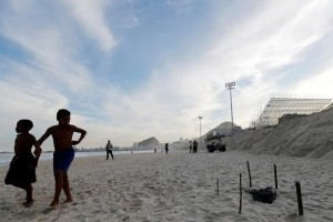 Children walks near a part of a mutilated body near the construction site of the beach volleyball venue for 2016 Rio Olympics on Copacabana beach in Rio de Janeiro, Brazil. Credit: Reuters/Sergio Moraes