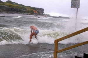 A swimmer is hit by a wave as he enters the water as severe weather, bringing strong winds and heavy rain, hits the eastern coast of Australia at Clovelly Beach in Sydney, June 5, 2016. Credit: Reuters/David Gray