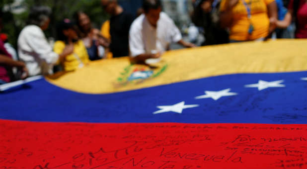 """A message written on a Venezuelan national flag that reads, """"Venezuela don't give up,"""" is seen during a gathering in Venezuela.  Credit: Reuters"""