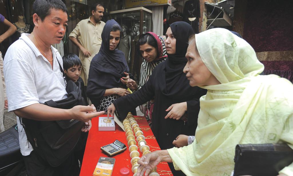Women buy jewellery from a Chinese vendor in Rawalpindi's Raja Bazaar. Credit: Tanveer Shehzad, White Star.
