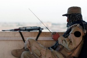 A private security organisation contractor listens to a radio while carrying out his duty at a guard tower at Camp Nathan Smith in Kandahar city, in this May 7, 2010 file photo. Credit: Reuters/Nikola Solic/Files