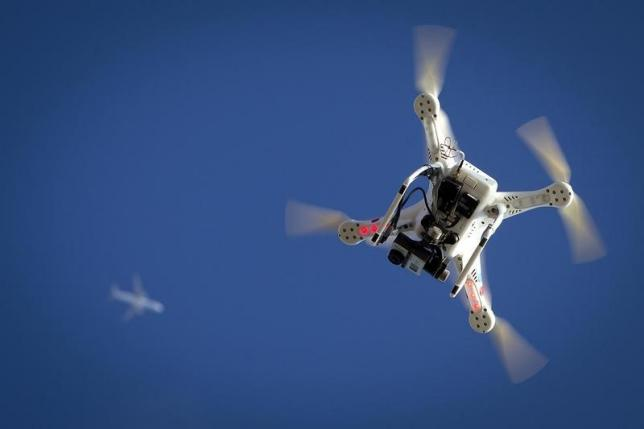 An airplane flies over a drone in the Brooklyn borough of New York January 1, 2015. Credit: Reuters/Carlo Allegri