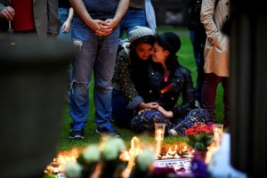 Mourners embrace during a candle-lit vigil, in memory of the victims of the gay nightclub mass shooting in Orlando, at St Anne's Church in the Soho district of London, Britain June 13, 2016. Credit: Reuters/Dylan Martinez