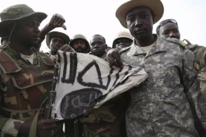 Nigerien soldiers hold up a Boko Haram flag they had seized in the recently retaken town of Damasak, Nigeria, March 18, 2015. Credit: Reuters/Emmanuel Braun