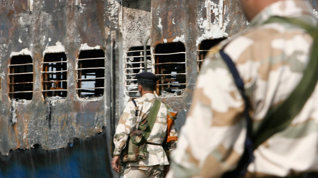 Police stand guard outside the burnt bogies of the Samjhauta Express. Credit: Reuters