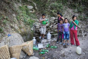Bir Bahadur Mager fetching water in  plastic bottle from a spring during dry season. These children had to walk half an hour to fetch water from this spring . Udyapur, Nepal