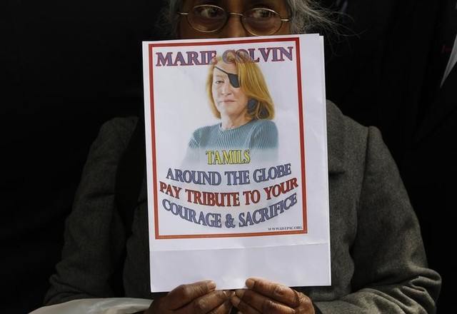 A woman holds a sign honoring Sunday Times journalist Marie Colvin after a memorial service, outside St Martin in the Field in London May 16, 2012. Credit: Reuters/Stefan Wermuth/FilesA woman holds a sign honoring Sunday Times journalist Marie Colvin after a memorial service, outside St Martin in the Field in London May 16, 2012. Credit: Reuters/Stefan Wermuth/Files