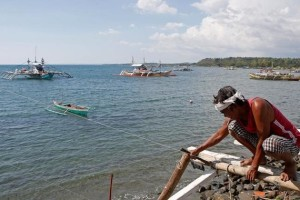 A fisherman repairs his boat overlooking fishing boats that fish in the disputed Scarborough Shoal in the South China Sea, at Masinloc, Zambales, in the Philippines April 22, 2015. Credit: Reuters/Erik De Castro/File Photo