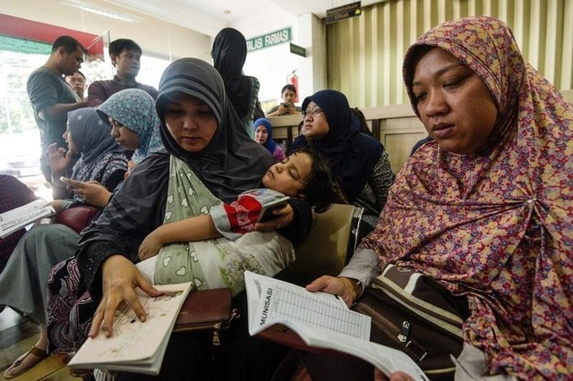 Women wait for information about the alleged use of fake vaccines on their children at a hospital in East Jakarta, Indonesia July 15, 2016. Credit: Reuters/ Antara Foto/Sigid Kurniawan/