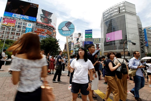 A member of the Students Emergency Action for Liberal Democracy (SEALDs) holds a placard calling on youths to vote in the July 10 upper house election, in front of a busy crossing in Shibuya district in Tokyo, Japan June 26. Credit: Reuters/Toru Hanai