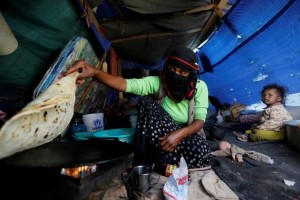 A woman makes bread inside her tent at a camp for internally displaced people near Sanaa, Yemen, May 24. Credit: Reuters/Khaled Abdullah/File Photo
