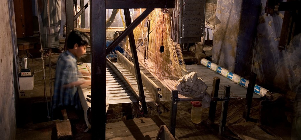 A child working in a loom. Credit: WikimediaCommons