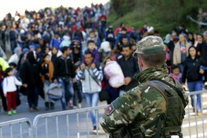 A member of the Sowenian army observes migrants walking towards the Austrian border near the village of Sentilj, Slovenia, October 24, 2015. Credit: Reuters