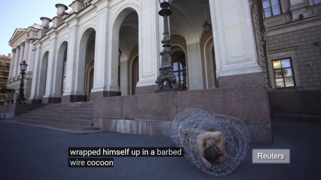Screenshot of Petr Pavlensky cocooned in barbed wire. Credit: Youtube/ Reuters