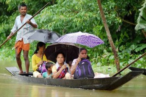 A flood affected family travel on a boat to a safer area. Credit: PTI
