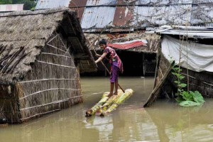 A woman crosses a flooded area over a raft made of banana tree trunks at Bura Bure in Morigaon district of Assam. Credit: PTI