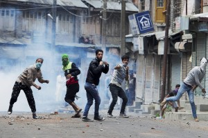 Srinagar: Protesters throw stones on police amid tear smoke during a clash in Srinagar on Sunday. Authorities imposed restrictions in most parts of Valley following the killing of  most wanted Hizbul Mujahideen commander, Burhan Muzaffar Wani, along with his two associates. PTI Photo by S Irfan   (PTI7_10_2016_000101B)