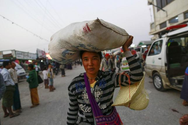 A woman, fleeing with her family from Laukkai, the capital of Kokang in Shan State, carries a sack as she arrives at Mandalay highway bus station, Myanmar,February 14, 2015. Credit: Reuters/Soe Zeya Tun