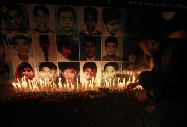 A man places a rose after lighting candles in front of portraits of the victims of the Taliban attack on the Army Public School in Peshawar, during a candlelight vigil in Lahore December 19, 2014. Credit: Reuters/Mohsin Raza