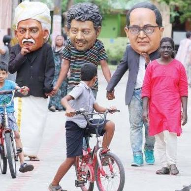 Children look on as Jaya walks the streets of Kochi with other artists. Credit: Facebook