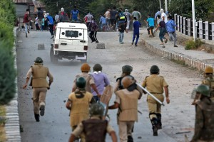 Security jawans chasing away stone throwing youths during a clash in Srinagar on Thursday. Credit: PTI/ S. Irfan