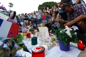 People gather near flowers and candles left as tribute to mourn the deaths of 84 people in Nice, France. Credit: Reuters