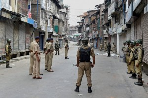 CRPF personnel guard a street during a strike on the fourth consecutive day in Srinagar on Tuesday. Authorities imposed restrictions in most parts of the Valley following the killing of  Hizbul Mujahideen commander, Burhan Muzaffar Wani, along with his two associates.  Credit: PTI