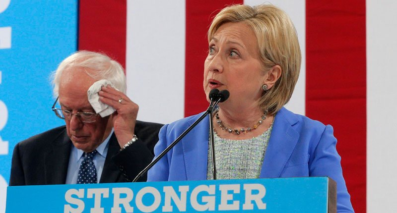 Democratic U.S. presidential candidate Hillary Clinton speaks as Senator Bernie Sanders wipes his forehead after he endorsed her during a campaign rally in Portsmouth, New Hampshire, U.S., July 12, 2016. Credit: REUTERS/Brian Snyder
