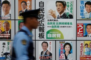 A police officer walks past Japan's ruling Liberal Democratic Party's (LDP) poster (2nd from right) for the July 10 upper house election with the image of Shinzo Abe, Japan's Prime Minister and leader of the LDP, and other candidates' posters at the LDP headquarters in Tokyo, Japan July 10. Credit: Reuters/Toru Hanai