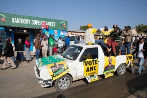An ANC party vehicle appeals for votes as locals are seen outside a voting station during the Local Government elections in Diepsloot township, north of Johannesburg, South Africa. August 3,2016. James Oatway, Reuters/Files