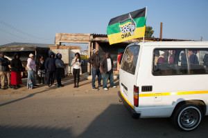 A taxi carrying the flag of the ruling African National Congress (ANC) party drives past locals queueing  to cast their votes during the Local Government elections in Diepsloot township, north of Johannesburg, South Africa. Credit: REUTERS/James Oatway
