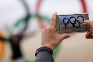 A woman takes pictures with a mobile phone in front of the Olympic rings placed at the Copacabana beach ahead of the 2016 Rio Olympics in Rio de Janeiro, Brazil July 21, 2016. REUTERS/Ueslei Marcelino - RTSJ0T2