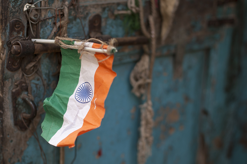 Fragile Freedom: A crumpled paper flag at a doorway in Ahmedabad. Credit: Meena Kadri/Flickr CC BY-NC-ND 2.0