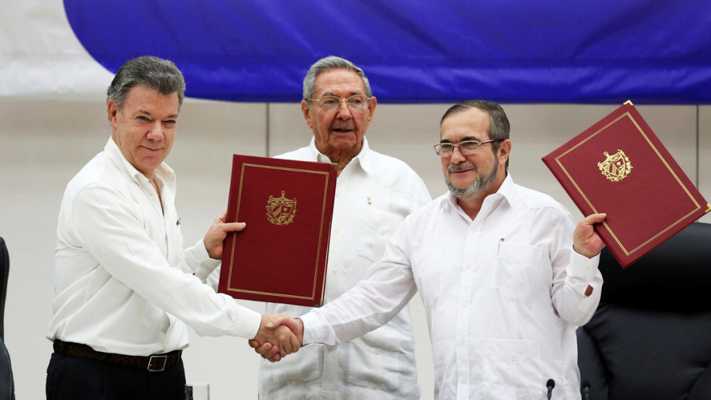 Colombian President Juan Manuel Santos, left, shakes hands with FARC rebel leader Rodrigo Londono, better known by his nom de guerre Timochenko, right, as Cuba's President Raul Castro looks on after the signing of a historic ceasefire deal between the Colombian government and FARC rebels in Havana, Cuba, on June 23, 2016. Credit: Reuters