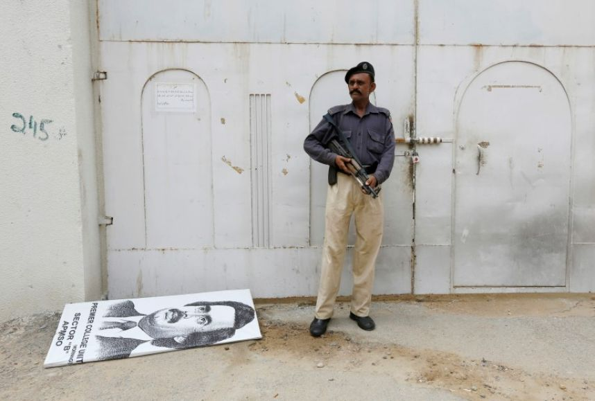 A policeman stands guard at an entrance gate with wax-sealed padlock, beside a poster depicting Altaf Hussain, leader of Muttahida Qaumi Movement (MQM) political party, after paramilitary forces sealed the headquarters in Karachi, Pakistan, August 23, 2016. Credit: REUTERS/Akhtar Soomro