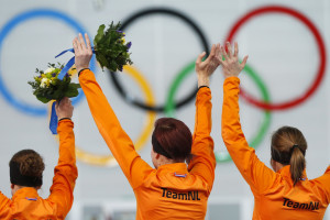 Second-placed Ireen Wust of the Netherlands (L), her compatriots winner Jorien ter Mors and third-placed Lotte van Beek celebrate on the podium during the flower ceremony for the women's 1,500 metres speed skating race in the Adler Arena at the Sochi 2014 Winter Olympic Games February 16, 2014. Mors won the women's 1,500 metres speed skating title in an Olympic record time on Sunday as the Dutch once again swept the medals at the Adler Arena. It was also a third speed skating medal sweep in Sochi for the Dutch after the men completed the feat in the 500 and 5,000m.  REUTERS/Issei Kato (RUSSIA  - Tags: OLYMPICS SPORT SPEED SKATING TPX IMAGES OF THE DAY)   - RTX18XSP