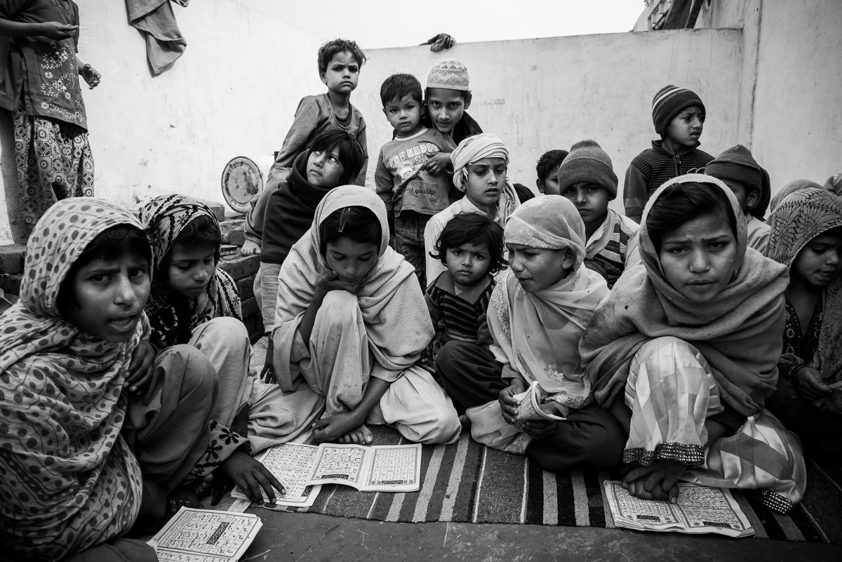 Children studying at a makeshift school imparting Quran recitation classes. In the absence of primary schools at the newly constructed rehabilitation colonies, such schools provided basic education facilities. March 2014, Muzaffarnagar. Credit: Asif Khan