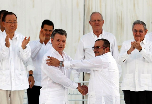 Colombian President Juan Manuel Santos (L) and Marxist rebel leader Rodrigo Londono (R), better known by the nom de guerre Timochenko, shake hands after signing an accord ending a half-century war that killed a quarter of a million people in Cartagena, Colombia September 26, 2016. Credit: Reuters