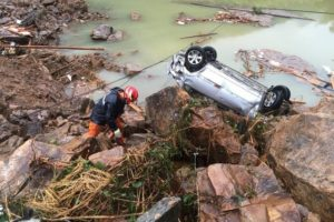 A rescue worker is seen next to an overturned car at the site of a landslide caused by heavy rains brought by Typhoon Megi, in Sucun Village, Lishui, Zhejiang province, China, September 29, 2016. Credit: Reuters/Stringer
