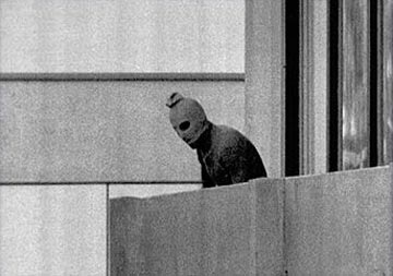 One of the most reproduced photos taken during the siege captured a kidnapper on the balcony attached to Munich Olympic village Building 31, where members of the Israeli Olympic team and delegation were quartered. Credit: AP/Wikimedia