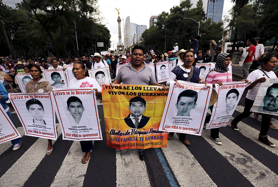 Relatives carry photos of some of the 43 missing students of the Ayotzinapa teachers' training college during a protest to mark the 11-month anniversary of their disappearance in Mexico City, Aug. 26, 2015. Credit: Reuters
