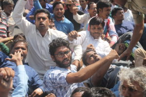 Protestors trying to save Jignesh Mevani and Hiten Makwana from being injured while being pulled by cops, Makwana in white check shirt. Picture credit: Damayantee Dhar