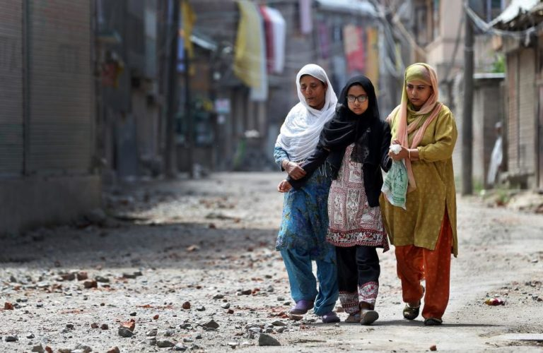 Two women and a girl make their way along a street littered with rocks thrown by protestors in Srinagar as the city remains under curfew following weeks of violence in Kashmir August 19, 2016. Credit: Cathal McNaughton/Reuters File Photo