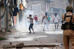 A protester throws back a tear gas shell fired by police during a protest in Srinagar. Credit: Reuters/Danish Ismail/Files