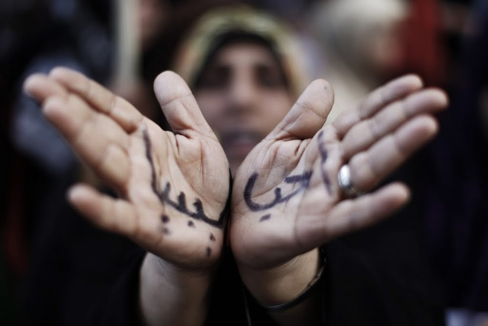"""File photo of a woman with the Arabic words for """"I love Libya"""" written on her hands in Benghazi, March 23, 2011. Credit: Reuters"""